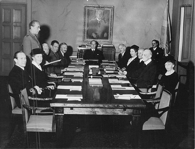 A black and white photo of people at a meeting.